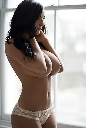 Busty brunette by the window